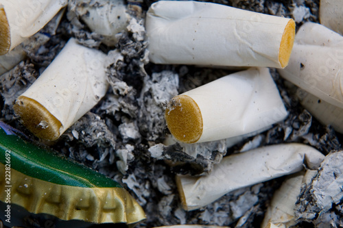 Fotografie, Obraz  The lid of the bottle and cigarette butts lie in the tobacco ash.