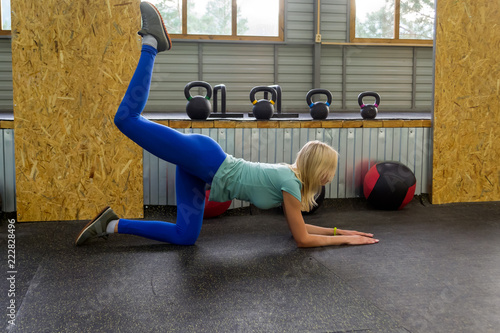 Deurstickers Ezel Slim young healthy sports girl doing the donkey kick exercise on all fours arching back straightening leg up concept sport, fitness, lifestyle. Kneeling on the floor and raising one leg up outdoors.