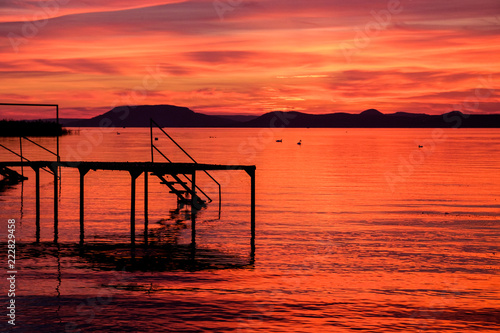 Foto op Canvas Baksteen silhouette of pier at red and hot sunset at Balaton lake - clouds, calm waves on water and hills in background - dark tones