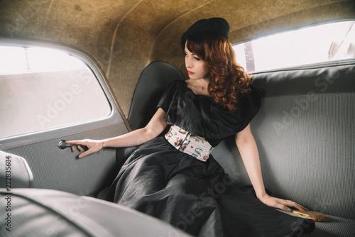 Femme en tenue retro dans une voiture ancienne