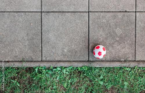 Valokuva  Roter Fußball auf Fließen und Gras