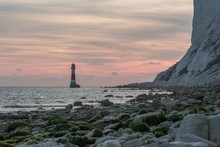 Beachy Head Lighthouse Near Eastbourne In United Kingdom While Red Sunset Behind The Lighthouse.