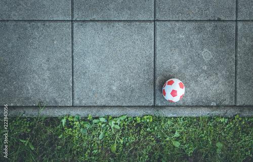 Roter Fußball auf Fließen und Gras Canvas-taulu