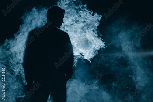 Fototapeta The man silhouette standing in the smoke. evening night time obraz