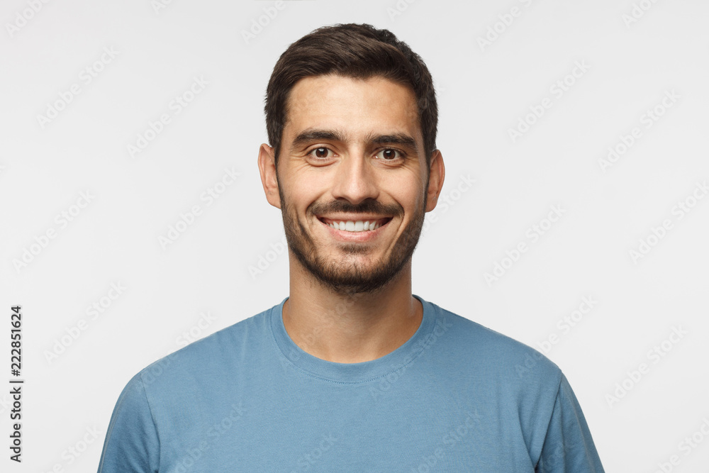 Fototapeta Close up portrait of young smiling handsome guy in blue t-shirt isolated on gray background