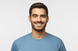 canvas print picture - Close up portrait of young smiling handsome guy in blue t-shirt isolated on gray background