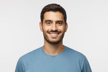 Close Up Portrait Of Young Smiling Handsome Guy In Blue T-shirt Isolated On Gray Background