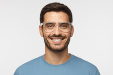 Close Up Shot Of Smiling Attractive Man In Blue T-shirt And Trendy Trasparent Eyeglasses Isolated On Gray Background