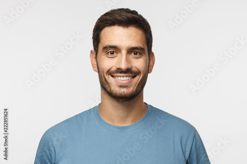 Leinwand Poster Close up portrait of young smiling handsome guy in blue t-shirt isolated on gray