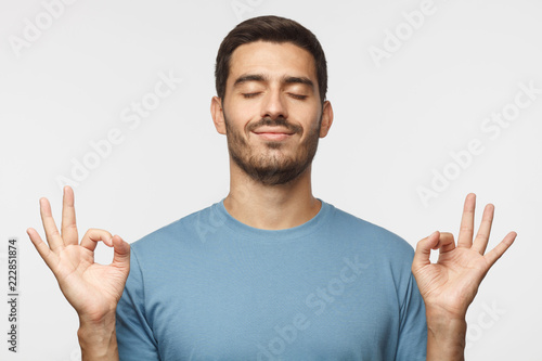 Fotomural  Happy smiling man standing with closed eyes, having relaxation while meditating, trying to find balance and harmony isolated