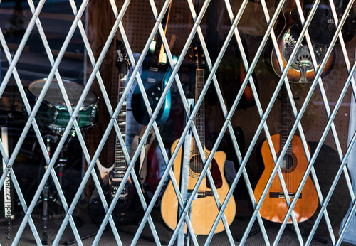 Photo Stands Music store Pawn shop window covered by bars