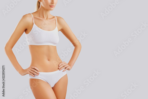 Obraz Slim body of a young woman in lingerie on a gray background. - fototapety do salonu