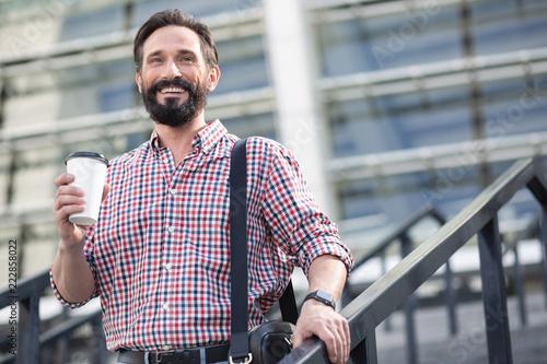 Fotografiet  Joyful bearded man walking down the stairs outdoors