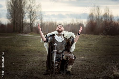 Fototapeta Knight raised his hands to the sky in pleading, wearing a chain mail