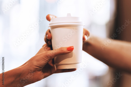 Fotografía  Barista passes coffee to a visitor in a popular coffee shop, hands and a glass of coffee are shot close-up