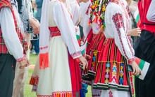 Unrecognizable Irls In Ethnic Bulgarian Costumes With Colorful Ornament Holding A Flag Of Bulgaria. Sunset At The Background
