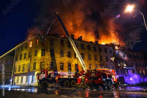 Fotografiet  Burning house at night, roof of building in flames and smoke, firefighter on cra