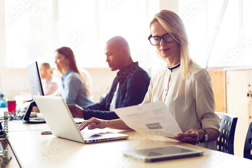 501f2301e61 Young modern colleagues in smart casual wear working while spending time in