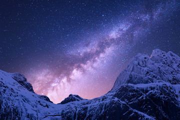 Fototapeta Niebo Milky Way above snowy mountains. Space. Fantastic view with snow covered rocks and starry sky at night in Nepal. Mountain ridge and sky with stars in Himalayas. Landscape with purple milky way. Galaxy