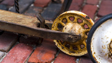 Close Up Of An Old Rusted Scooter Wheel With Bricks Background.
