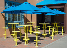Yellow Tables With Blue Umbrel...