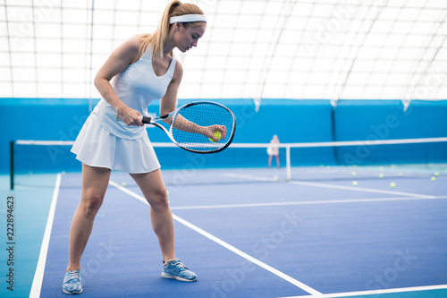 Side view  full length portrait of female tennis player ready to serve ball and holding racket in indoor court, copy space