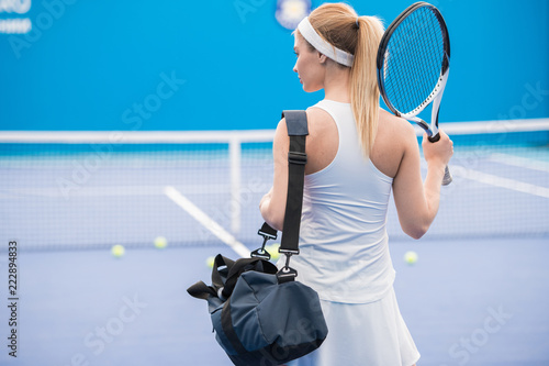Back view portrait of beautiful blonde woman entering tennis court for practice, copy space