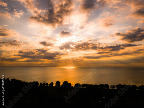 Gorgeous panoramic sunrise view with rays shining down over lake Michigan with colorful orange and blue cloudy sky above reflecting on the water below and tree lined shoreline in the foreground.