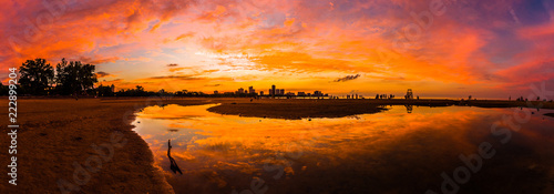 Tuinposter Beautiful, bright, saturated, and vivid sunset with colorful orange, yellow, blue, pink and purple clouds in the sky above reflecting on rain puddles in the sand at Montrose Beach in Chicago Illinois.