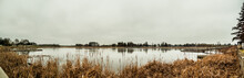 Beautiful Outdoors Landscape Nature Panorama Of Cattail Reeds And Pine Trees Lining The Calm Waters Of A River Or Lake In Warroad Minnesota With Cloudy White And Gray Sky Above.