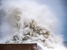 Photograph Of A Large Wave From Lake Michigan Crashing Into Concrete Wall Barrier And Splashing And Spilling Over The Edge With Blue Sky Beyond Making A Dramatic Background Photograph.
