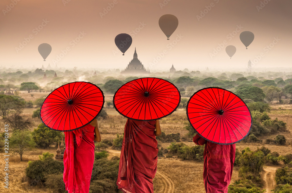 Fototapeta Back side of three Buddhist novice are walking over the Ancient Temples in Bagan with hot air on the sky at sunrise time, Myanmar