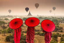 Back Side Of Three Buddhist Novice Are Walking Over The Ancient Temples In Bagan With Hot Air On The Sky At Sunrise Time, Myanmar
