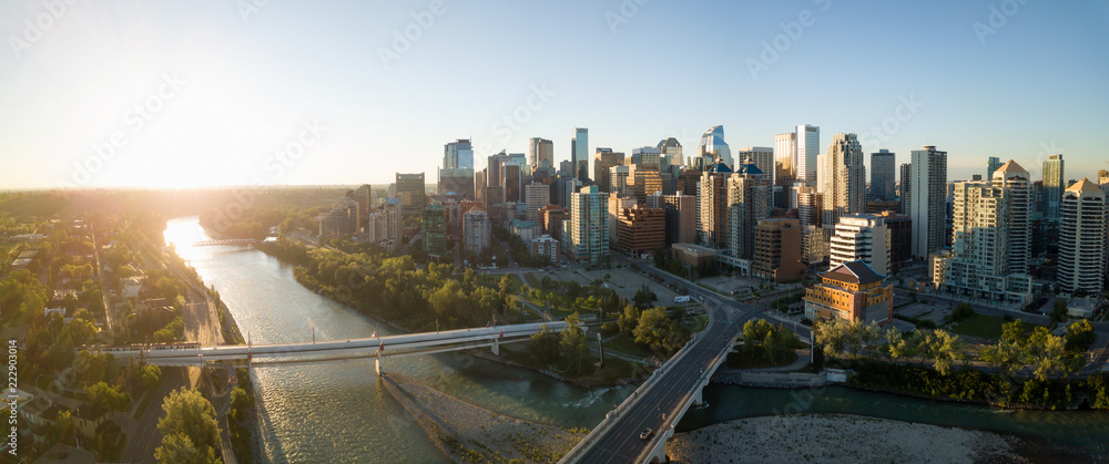 Fototapeta Aerial panoramic view of a beautiful modern cityscape during a vibrant sunny sunrise. Taken in Calgary Downtown, Alberta, Canada.