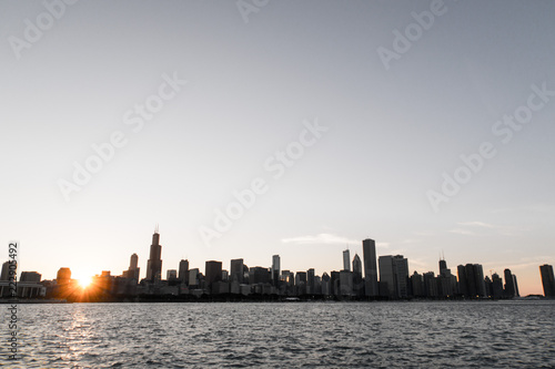 Foto op Plexiglas Chicago Chicago skyline picture during beautiful sunset with building silhouettes and rippling waves of Lake Michigan water in the foreground