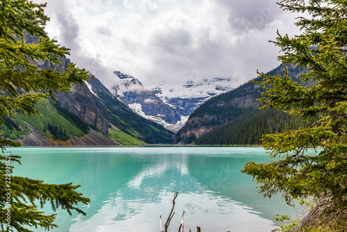 Poster Bergen Lake Louise framed by trees with reflection leading to mountains and cloudy sky Canada