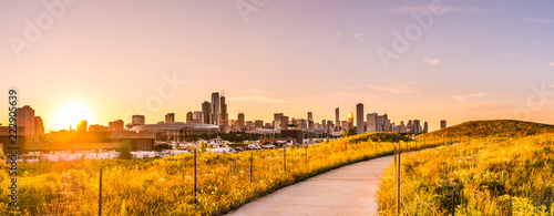 Poster Chicago Chicago landscape photo at Northerly Island looking down curved path during beautiful sunset with wildflowers and grass in foreground at golden hour and building skyline at the horizon