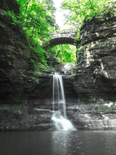 Beautiful Waterfall View At Mattiessen State Park In Illinois View Overlooking The Pool Of Water Below With Water Cascading Down The Limestone Cliff Walls And Bridge Beyond With Green Trees Above