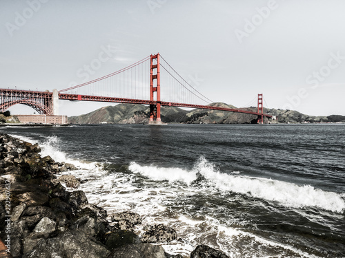 Photo  Golden Gate bridge with waves crashing against rocks in the foreground along the San Francisco Bay in California