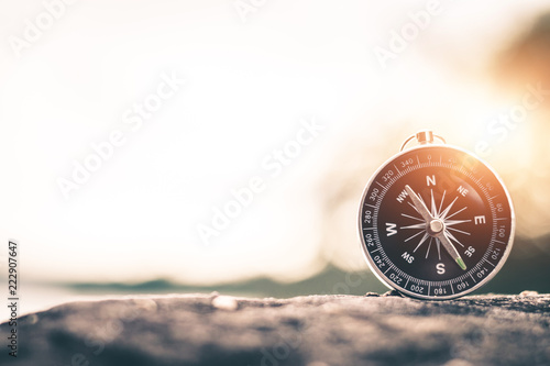 Compass of tourists on mountain at sunset sky. Fototapeta