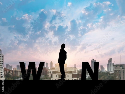 Photo Silhouette business man on city background  and WIN message