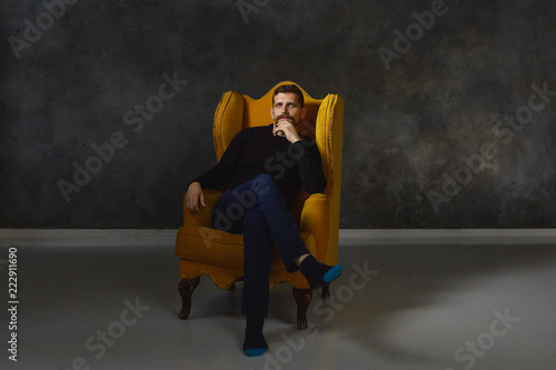 Fotografie, Obraz Isolated indoor shot of handsome confident man with beard sitting comfortably in luxurious yellow armchair wearing elegant black clothes and shoes