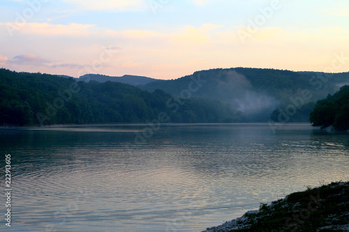 Fotografia  The cute still lake water at sunset with green hills in distance