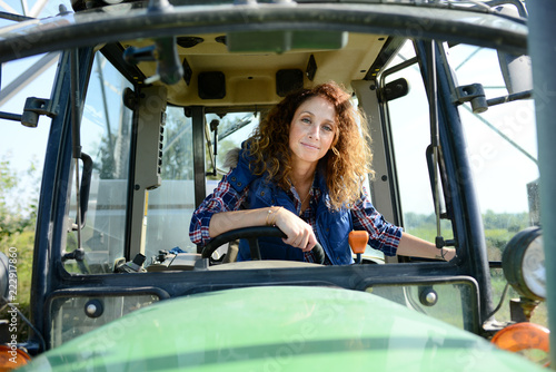 beautiful woman female farmer driving tractor in countryside field Fototapete