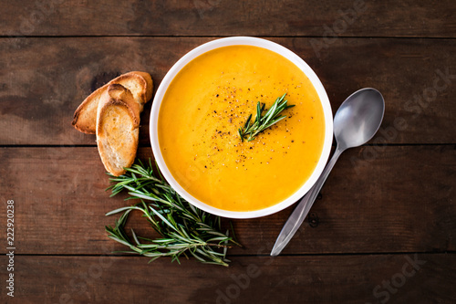 Pumpkin and carrot  Cream soup on  wood rustic  background. Autumn cream-soup in country style. Top view. Copy space.