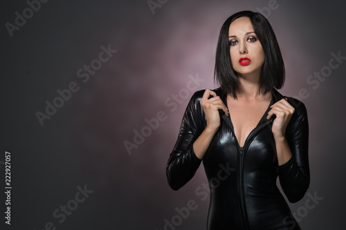 Fotografia, Obraz  Beautiful woman in latex suit on a dark