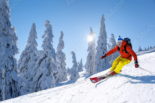 Valokuva Skier skiing downhill in high mountains against blue sky
