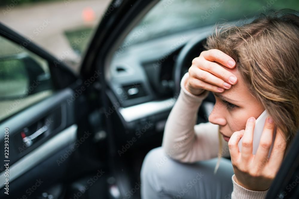 Fototapeta Young woman in the damaged car after a car accident, making a phone call.