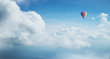 Leinwandbild Motiv Colorful hot air balloon flying against blue cloudy sky.