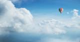Kolorowy gorące powietrze balon latający przeciw błękitnemu chmurnemu niebu. - 222938897
